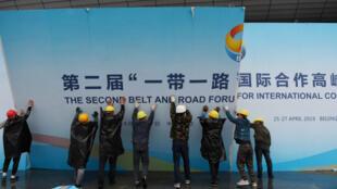 Des employés retirent un panneau à l'extérieur du deuxième forum consacré au projet chinois des Nouvelles routes de la soie, à Pékin, le 27 avril 2019.