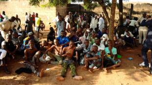Algunos de los liberados por la policía se sientan en el suelo en Ibadan, Nigeria en una fotografía dada a los medios de comunicación por las autoridades policiales.