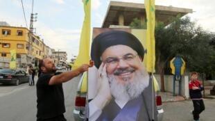 Un hombre ajusta la bandera de Hezbolá en un vehículo decorado con un póster del líder de Hezbolá del Líbano Sayyed Hassan Nasrallah en la aldea sureña de Kfar Kila.