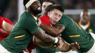 Wales' Josh Adams is tackled by South African players, October 27, 2019.