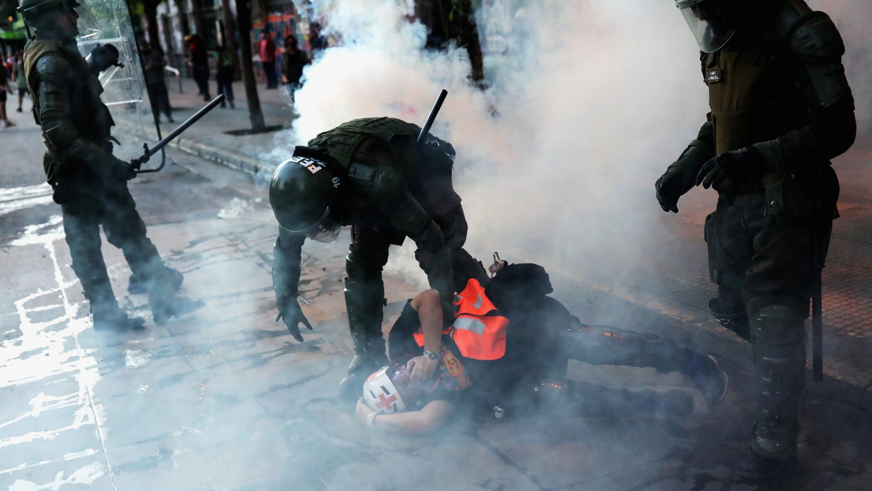 Un policier anti-émeute arrête un secouriste lors de manifestations à Santiago, au Chili, le 6 novembre 2019.