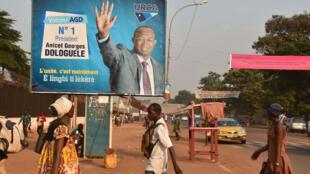 Des passants devant l'affiche du candidat Anicet Georges Dologuélé arrivé en tête du premier tour de la présidentielle en Centrafrique.