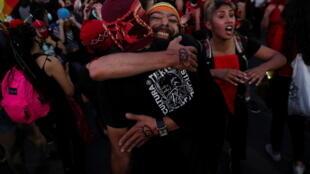 Des Chiliens s'enlacent pour célébrer le vote favorable à la rédaction d'une nouvelle Constitution, le 25 octobre 2020, à Santiago.