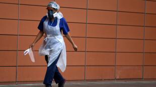 ممرضة تضع قناعا واقيا بينما تمر من أمام مستشفى لندن الملكي بتاريخ 18 نيسان/أبريل 2020