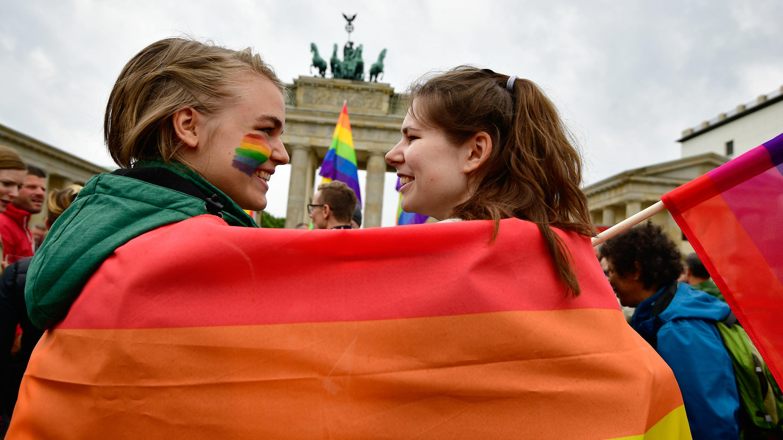 Dos jóvenes envueltas en una bandera de la diversidad durante un desfile por el orgullo homosexual frente a la Puerta de Brandemburgo en Berlín. Archivo, 30 de junio de 2017.