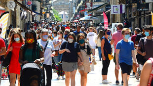 People stroll down Bordeaux's main shopping street Sainte-Catherine, where wearing a mask is compulsory as of August 15, 2020, to prevent the spread of the novel coronavirus COVID-19.