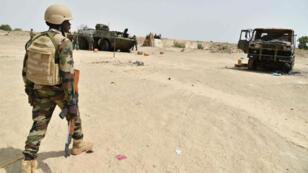 Un soldat nigérien devant des véhicules de l'armée endommagés le 17 juin 2016, lors d'une attaque au camp militaire de Bosso.