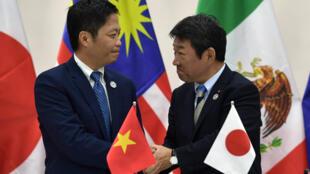 Le ministre vietnamien du Commerce, Tran Tuan Anh, serre la main du ministre japonais de l'Économie, Toshimitsu Motegi.