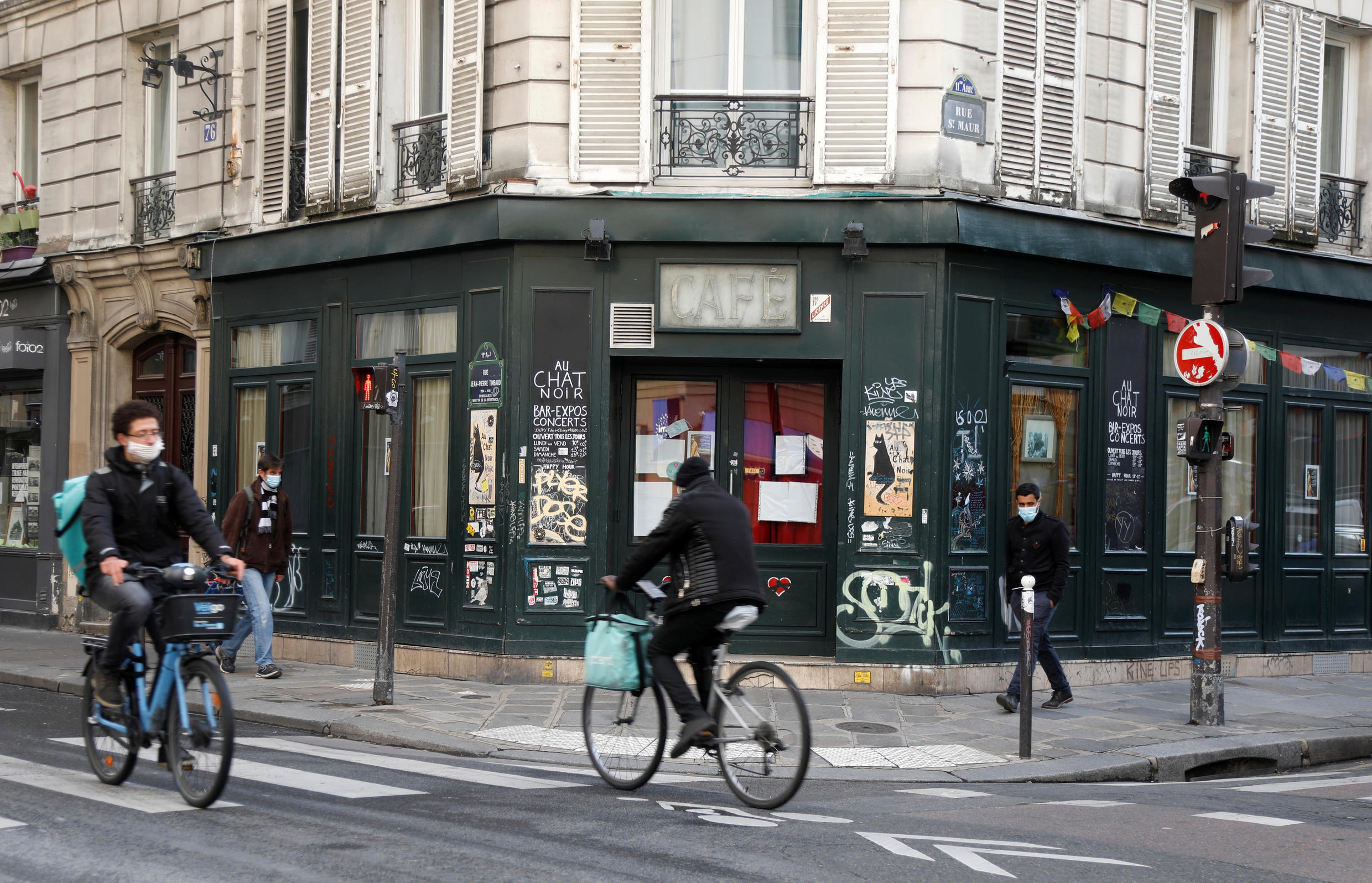 Cyclists ride past the Au Chat Noir bar, which was closed as part of stricter restrictions due to the spread of Covid-19, in Paris, France on October 13, 2020.