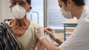 Un médecin vaccine un patient contre le Covid-19, le 20 février 2021 au Nouvel hôpital Civil de Strasbourg, dans le cadre d'un programme de vaccination de greffés du coeur et de patients en attente de transplantation