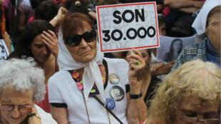 Una mujer sostiene un cartel que hace referencia a los 30.000 desaparecidos de la dictadura militar.