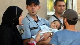 شرطي كرواتي يحمل طفلا لأسرة مهاجرين في قرية توفارنيك قرب الحدود الصربية الكرواتية.