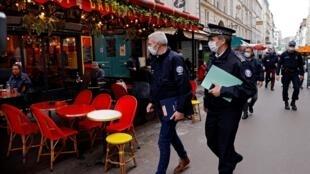 Des policiers patrouillant pour faire respecter les mesures sanitaires dans une rue de restaurants à Paris le 6 octobre 2020