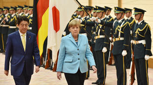 German Chancellor Angela Merkel (right) and Japanese Prime Minister Shinzo Abe (left) review the honour guards  in Tokyo on March 9, 2015