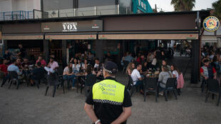 Un policier surveille le respect de consignes anticoronavirus dans un restaurant de Malaga le 23 mai 2020