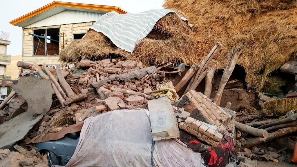 Un automóvil yace dañado debajo de las ruinas, luego de que un terremoto azotara la aldea de Varankesh en la provincia oriental de Azerbaiyán, al noroeste de Teherán