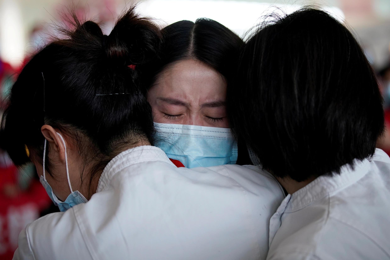 Archivo: personal médico se abraza tras la orden de levantar las restricciones de viaje por coronavirus parte de las autoridades. Wuhan, China, el 8 de abril de 2020.