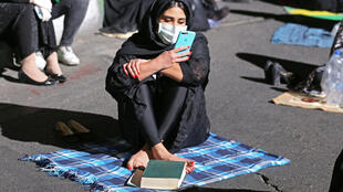 An Iranian woman wearing a face mask against the novel coronavirus prays outside a Tehran mosque during the Muslim fasting month of Ramadan