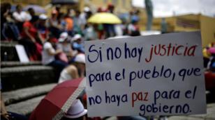 """""""Si no hay justicia para el pueblo, no hay paz para el gobierno"""", dice un letrero durante una marcha del empleado del sector público en huelga indefinida contra una reforma tributaria propuesta por el gobierno de Costa Rica."""