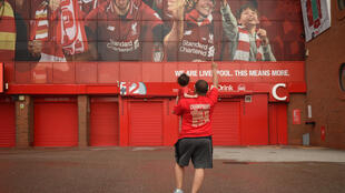 Un supporteur de Liverpool et son enfant devant le stade d'Anfield, le 26 juin 2020 après le titre de chalmpion remporté par les Reds