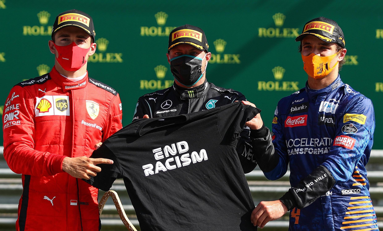"""Le monégasque Charles Leclerc (gauche), le Finlandais Valtteri Bottas (centre) et le Britannique Lando Norris (droite) posent avec un t-shirt """"End Racism"""" sur le podium du Grand Prix remporté dimanche 5 juillet, en Autriche, par Valtteri Bottas."""