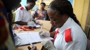 Una trabajadora de salud congoleña registra los datos médicos de los pasajeros en el aeropuerto de Mbandaka, República Democrática del Congo, el 19 de mayo de 2018.