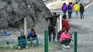 مهاجرون شبان ينتظرون في 16 آب/أغسطس 2017 قرب تلة في كاليه في شمال فرنسا..