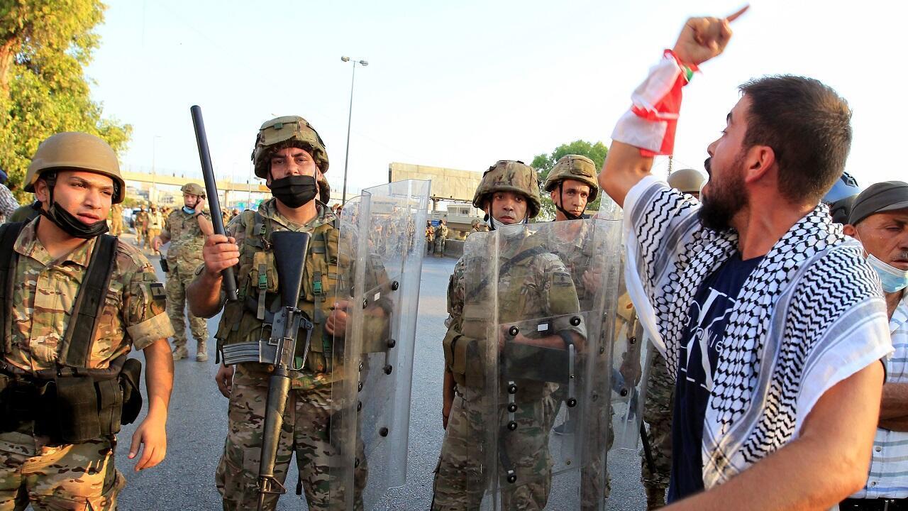 متظاهر أمام جنود الجيش اللبناني خلال مسيرة مناهضة للحكومة قرب القصر الرئاسي في بعبدا. لبنان في 12 سبتمبر/أيلول 2020.