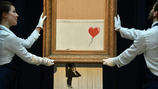 "D'abord baptisé ""Girl with Balloon"", la toile de Banksy a été renommée ''Love is in the bin"" après son autodestruction partielle."