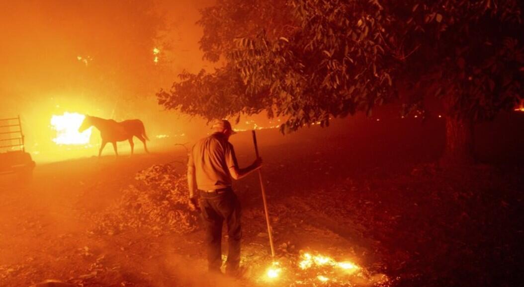 Un hombre intenta salvar su hogar de las llamas del incendio en denominado LNU Lighting Complex, en Vacaville California, el 19 de agosto de 2020.