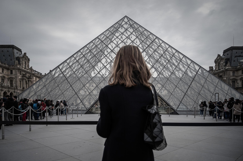 Archivo: Una mujer se para frente a la icónica pirámide del Museo del Louvre el 4 de marzo de 2020, en París, Francia.