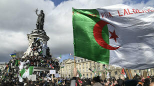 À Paris, place de la République, un drapeau algérien est brandi lors de la manifestation contre la candidature d'Abdelaziz Bouteflika à un cinquième mandat, le 10mars2019.