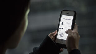 Un utilisateur chinois d'iPhone consulte l'application du New York Times en 2015.