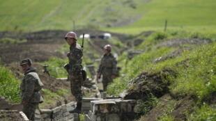 جنود من أصل أرمني يقفون في خندق في موقعهم بالقرب من بلدة مارتوني في ناغورنو كاراباخ في أبريل 2016.