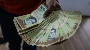 Un hombre muestra un fajo de billetes de bolívares soberanos, en Caracas, el 9 de octubre de 2019.