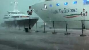 This photo grabbed from a video taken on July 7, 2019 and obtained on July 8, 2019 from Roberto Ferrucci (www.robertoferrucci.com) shows the 292-meter-long Costa Deliziosa cruise ship (right) close to a yacht (left) as it left Venice