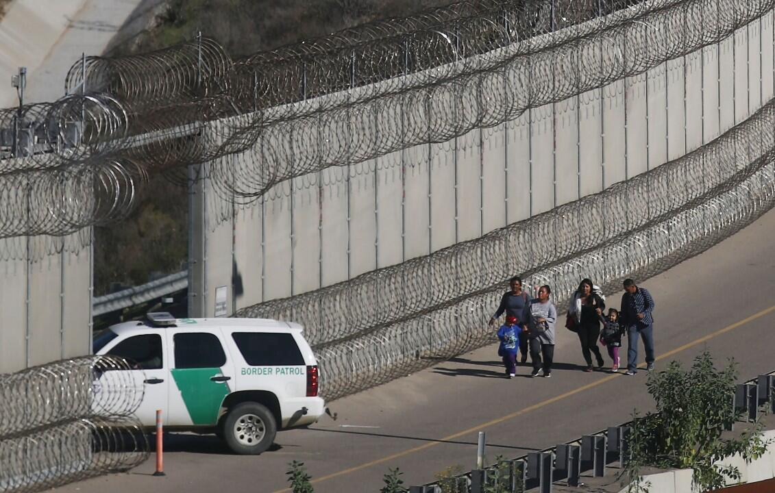Los migrantes caminan en el lado estadounidense de la frontera que divide a México con Estados Unidos mientras son detenidos por la Patrulla Fronteriza de ese país.