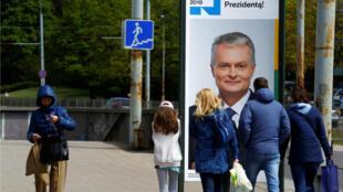 La gente pasa frente al cartel de la campaña del candidato presidencial lituano, Gitanas Nauseda, en Vilna, Lituania, el 9 de mayo de 2019.