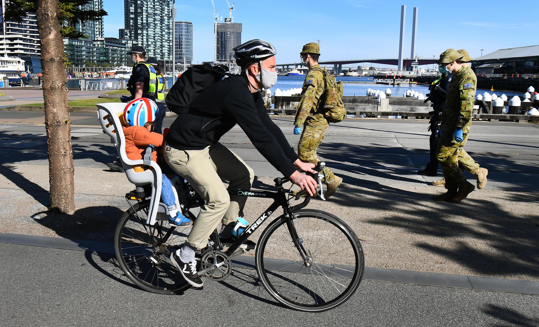 Un ciclista pasa junto a un grupo de policías y soldados patrullando en Melbourne, Australia, el 2 de agosto de 2020.