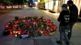 صورة ملتقطة في 30 أغسطس/آب 2018 لأشخاص يزورون ضريح ألماني قتل بمدينة كيمنتس شرق المانيا