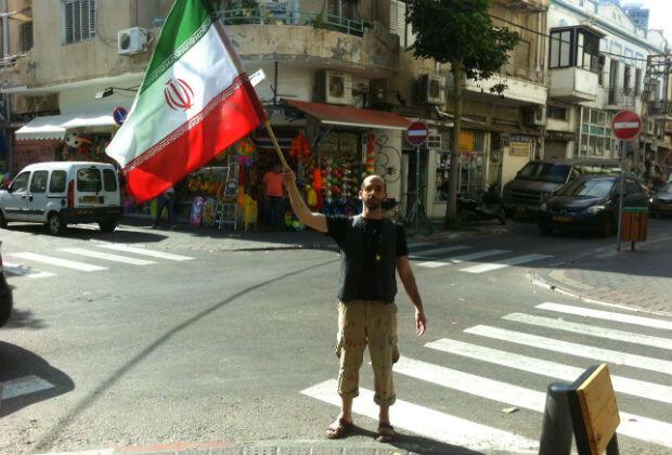 """Matan Pinkas avec un drapeau iranien à Jérusalem pour promouvoir l'ouverture d'une """"ambassade"""" d'Iran en Israël, juin 2015."""