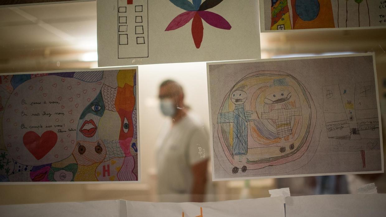 طبيب بالمركز الطبي الجامعي بمدينة نانت يمر بالقرب من رسومات أرسلها أطفال لتشجيع الأطقم الطبية. 19 مايو/أيار 2020.
