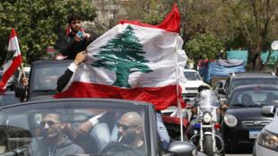 لبنانيون يرفعون العلم اللبناني خلال احتجاجات في سيارات ضد الطبقة السياسية في صيدا جنوب لبنان، 21 نيسان/أبريل 2020
