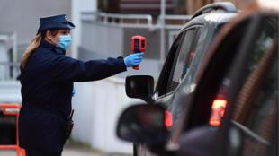 Una mujer toma la temperatura a un empleado de Fiat que accede en automóvil a la fábrica de Mirafiori, en la ciudad de Turín, el 27 de abril de 2020, tras el permiso del Gobierno italiano para reabrirla parcialmente
