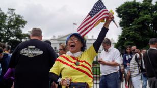 Victoria Kim, una partidaria vietnamita de Trump en California, iza una bandera estadounidense durante una vigilia frente a la Casa Blanca para celebrar la cumbre conjunta entre Donald Trump y Kim Jong-un celebrada en Singapur, Washington, EE. UU., el 11 de junio de 2018.