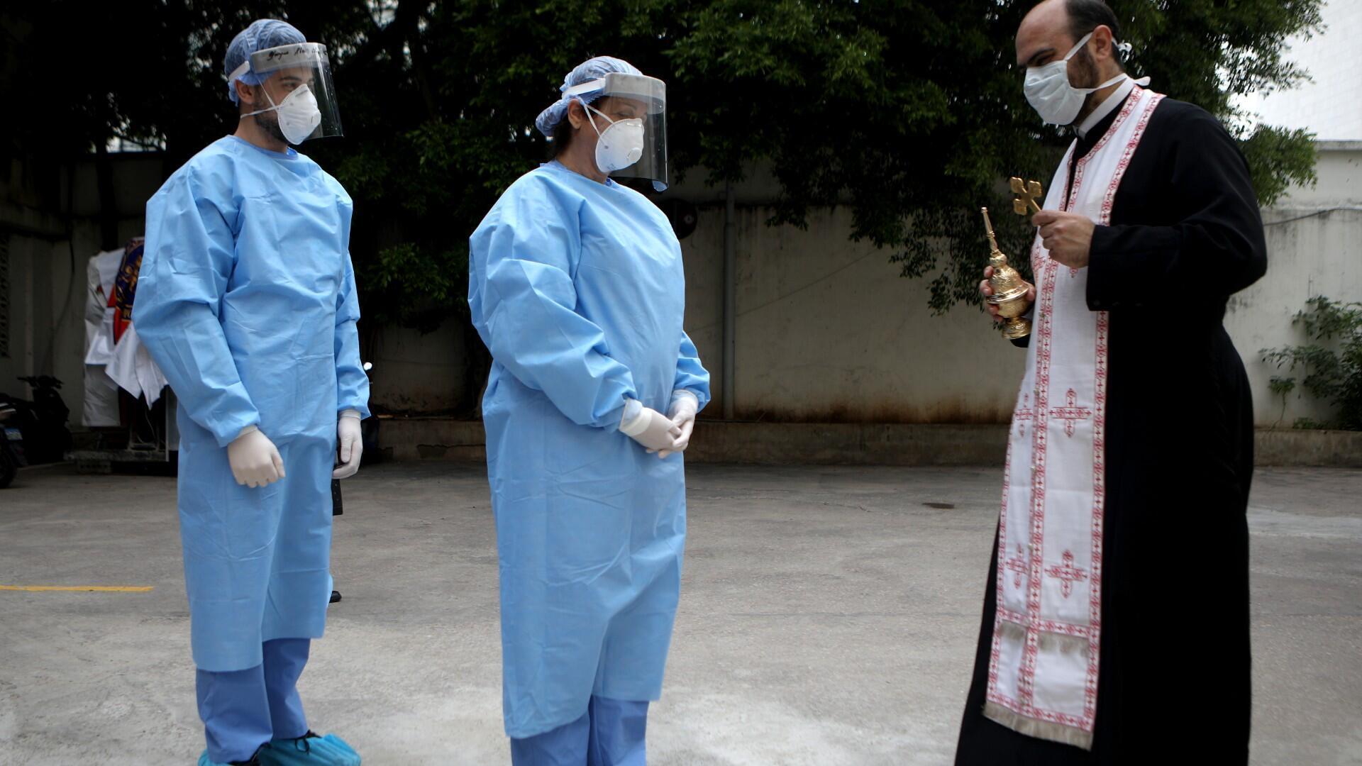 Un sacerdote ortodoxo griego libanés bendice a los miembros del Centro Médico de la Universidad del Hospital Saint George a cargo de pacientes con coronavirus COVID-19, en Beirut, capital de Líbano, el 24 de abril de 2020.