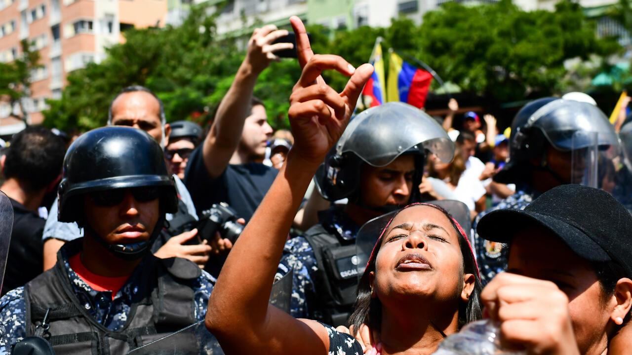 Des partisans du leader de l'opposition et président autoproclamé par intérim, Juan Guaido, manifestent devant des officiers de la police nationale bolivarienne à Caracas, le 9 mars 2019.