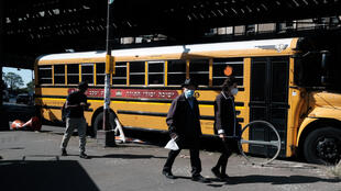 People walk by school buses in the neighborhood of Borough Park in Brooklyn, New York, on October 5, 2020. Borough Park is one of the nine New York City neighborhoods where nonessential businesses and schools are set to close Tuesday.