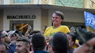Brazil's then-presidential candidate Jair Bolsonaro grimaces after being stabbed during a campaign rally in Juiz de Fora, in southern Brazil, on September 6, 2018