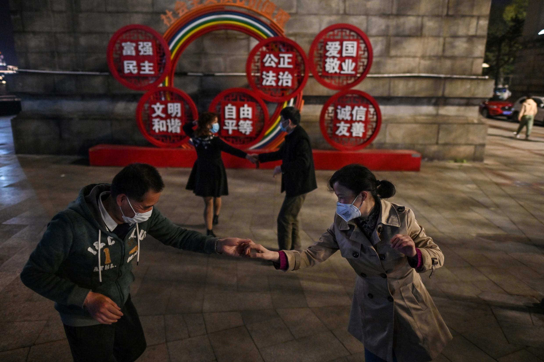 Varias parejas, que llevan mascarillas protectoras, bailan en un parque cercano al río Yangtsé, en Wuhan, en la provincia china de Hubei, el 13 de abril de 2020.